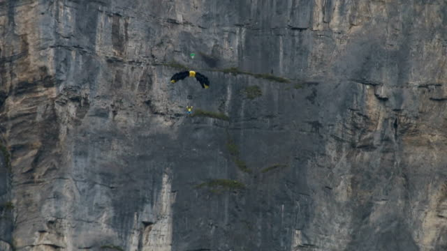 base jumper/wing suit flier descends from cliff - jumper stock videos and b-roll footage