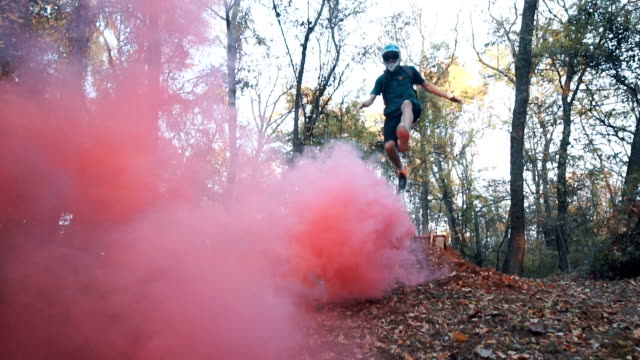 Jumping across red smoke in the forest