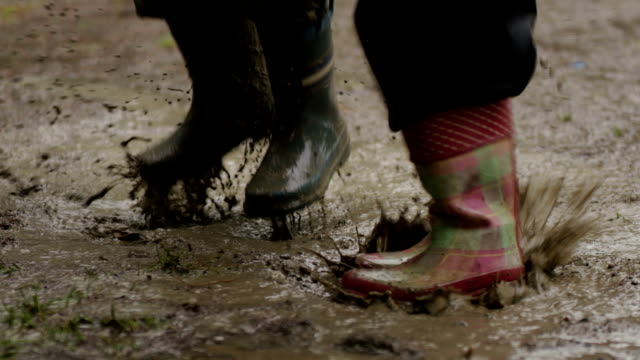 Jumping in a mud puddle with rain boots