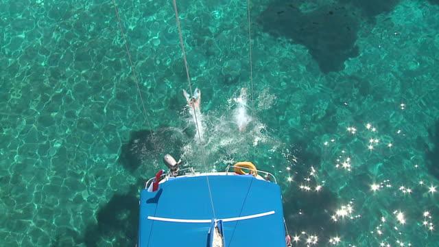 hd: saltare in acqua - barca da diporto video stock e b–roll