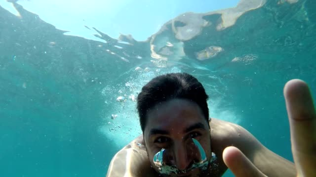 jumping into the water while taking yourself with your own camera - underwater camera stock videos & royalty-free footage