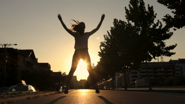 jumping jacks and jogging are best workout. silhouette of young woman exercising during sunset - star jump stock videos & royalty-free footage