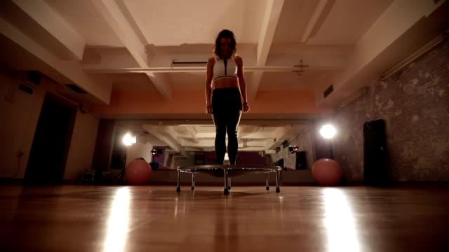 jumping on a mini-trampoline - pedana elastica per saltare video stock e b–roll