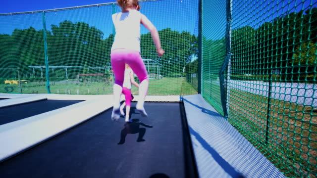 springen auf einem trampolin in einen park-spielplatz - kind im grundschulalter stock-videos und b-roll-filmmaterial
