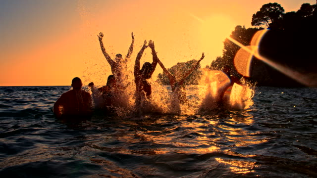 slo mo jumping out of the sea at dusk - group of people stock videos & royalty-free footage