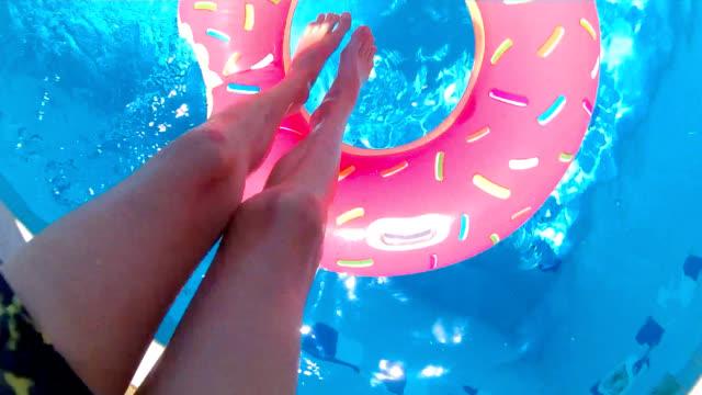 vídeos de stock, filmes e b-roll de pulando através do anel inflável - piscina