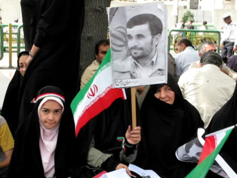 10 jun 2009 ms pan crowd of people holding placards and posters sitting on street curb during political demonstration / teheran iran / audio - auf dem boden sitzen stock-videos und b-roll-filmmaterial