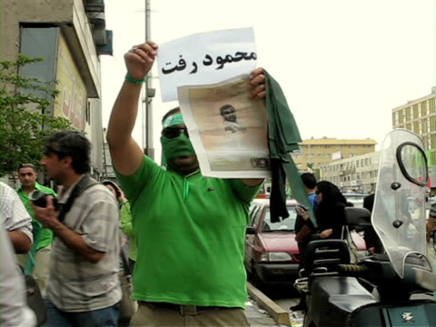 jun 2009 demonstrator holding poster and sign on standing amongst pedestrians on street / teheran, iran / audio - human limb stock videos & royalty-free footage