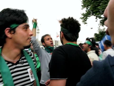 stockvideo's en b-roll-footage met jun 2009 demonstrators walking on street, cheering an shouting / teheran, iran / audio - menselijke arm