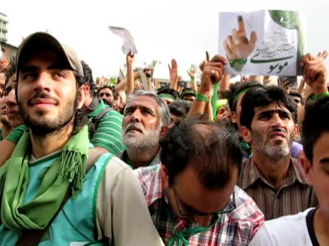 jun 2009 large group of men, dressed in green, demonstrating on street / teheran, iran / audio - berretto da baseball video stock e b–roll