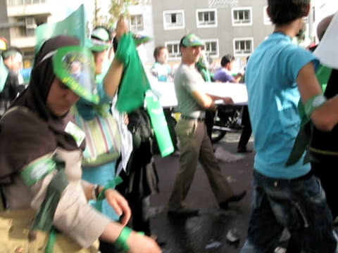 10 Jun 2009 POV MS Large group of people carrying green flags and posters walking in street demonstration / Teheran Iran / AUDIO