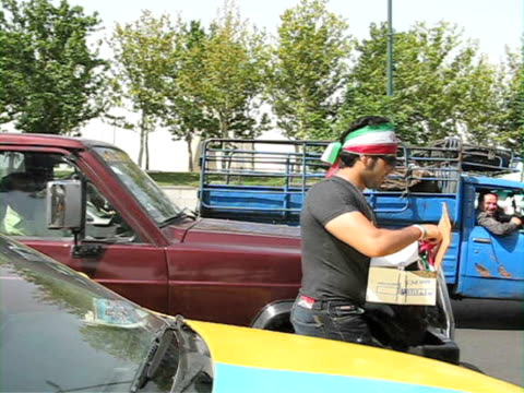 jun 2009 man giving away iranian bandanas to drivers on highway / teheran, iran / audio - hair accessory stock videos & royalty-free footage