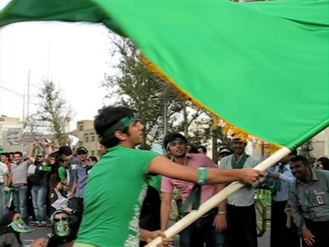 10 Jun 2009 MS Man spinning with large green flag amongst demonstrators on city square / Teheran Iran / AUDIO