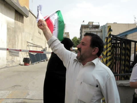 10 jun 2009 ms pov political activist holding iranian flag shouting on sidewalk / teheran iran / audio - human limb stock videos & royalty-free footage
