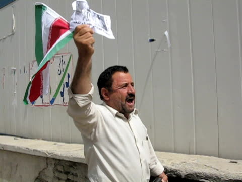 10 jun 2009 ms pov political activist holding iranian flag walking on street / teheran iran / audio - menschlicher arm stock-videos und b-roll-filmmaterial