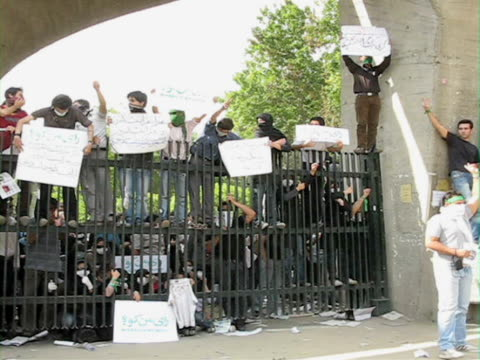 jun 2009 shake large group of people holding placards climbing on gate / teheran, iran / audio - human limb stock videos & royalty-free footage