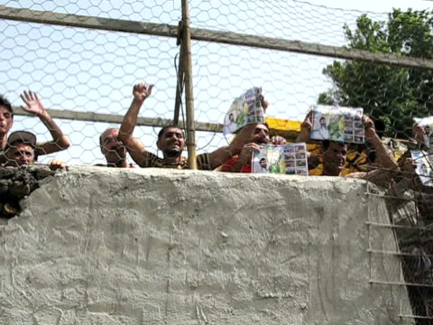 10 Jun 2009 MS PAN SHAKY LA Group of shouting men standing behind fence holding political fliers / Teheran Iran / AUDIO