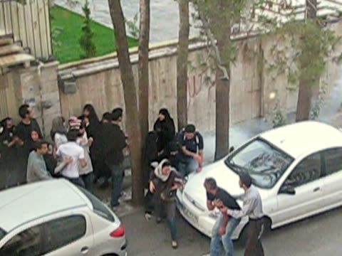 28 jun 2009 ms shaky pan zi riot police using smoke bombs dispersing demonstrators on street / teheran iran / - teheran stock-videos und b-roll-filmmaterial