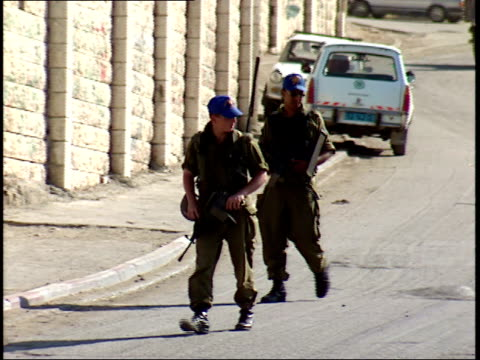 june 1 1996 ts israel security forces soldiers patrolling beside a high city wall with pedestrians wearing ghutrah headdresses walking past / israel - ornamento del capo video stock e b–roll