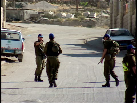 june 1, 1996 israel security forces soldiers patrolling beside a high city wall, with cars making u-turns rather than stop for the roadblock / israel - israeli military stock videos & royalty-free footage