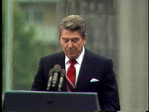 june 12, 1987 ronald reagan speaking from behind lectern about the fall of berlin wall / berlin, germany / audio - moving down video stock e b–roll