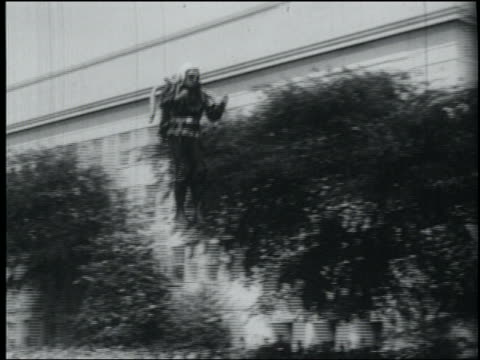 B/W June 15, 1961 PAN man (Harold Graham) with jet pack flying + landing in grass with audience and Pentagon building in background / Arlington, Virginia