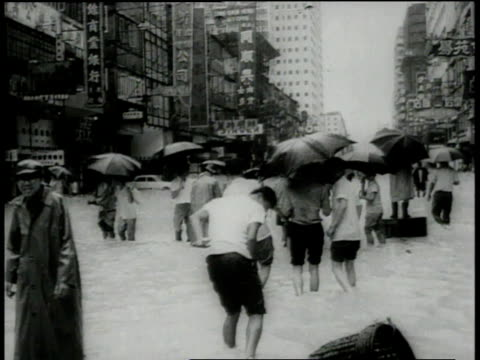 june 16 1966 montage hong kong downtown with people wading through streets under umbrellas washed out streets water running through washed out area /... - 1966 stock videos & royalty-free footage