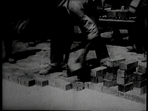june 1926 montage ernest vicknell laying bricks for a road very quickly / galesburg, illinois, united states - paving stone stock videos and b-roll footage