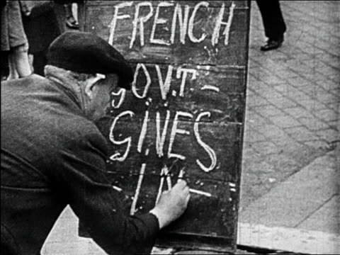 b/w june 1940 man writing on chalkboard french govt gives in / educational - solo un uomo anziano video stock e b–roll