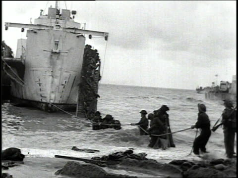 june 1944 group of sailors wedging buoy between rocks as jeeps are being unloaded onto shore past burning german tank / normandy, france - 1944 bildbanksvideor och videomaterial från bakom kulisserna