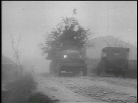 vidéos et rushes de b/w june 1950 tilt up pan soldiers in truck drive past camera on dirt road / start of korean war / news - véhicule utilitaire léger