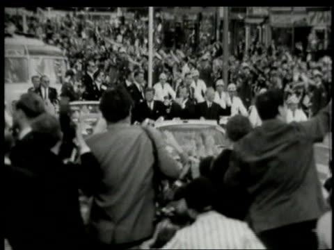 june 1963 john f. kennedy's motorcade passing huge crowds of cheering and waving germans / west berlin, germany - 西ドイツ点の映像素材/bロール