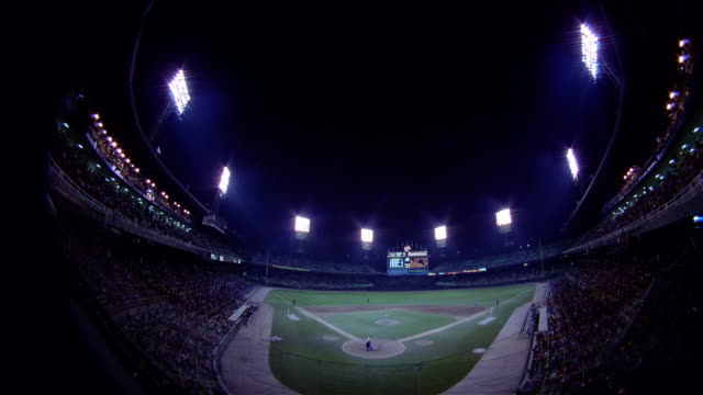 june 2, 1983 fish-eye fast motion shot of night game between chicago white sox and kansas city royals at comiskey park / chicago, illinois - スコアボード点の映像素材/bロール
