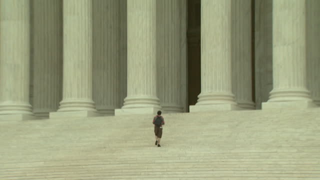 June 2 2009 ZO Visitor ascending the steps to the western entrance of the United States Supreme Court building / Washington DC United States