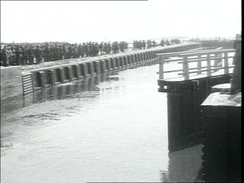 opening of the canal filled w/ water Workers have a swim Vs of water passing dam WS of dam Newly built houses locks armed soldier mounts guard Dikes...