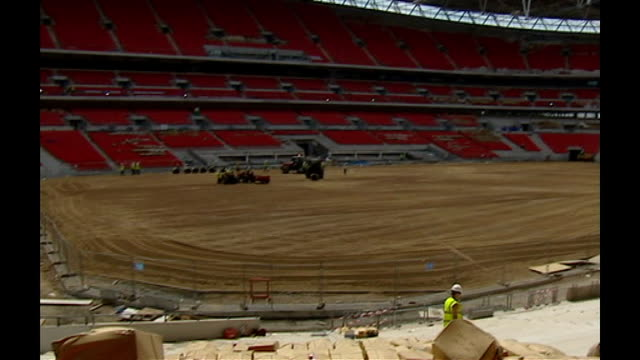 r12060622 / june 2006 interior of wembley stadium with unfinished pitch workers laying turf on pitch - turf stock videos & royalty-free footage