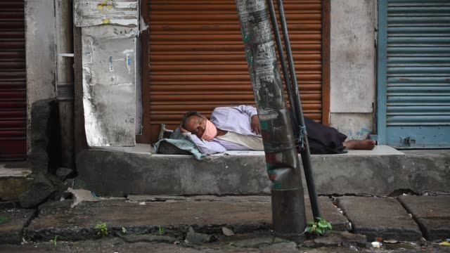 vídeos de stock, filmes e b-roll de june 2020. a man sleeping in front of a closed store during a total lockdown imposed by the assam government to contain the spread of coronavirus, in... - câmara parada