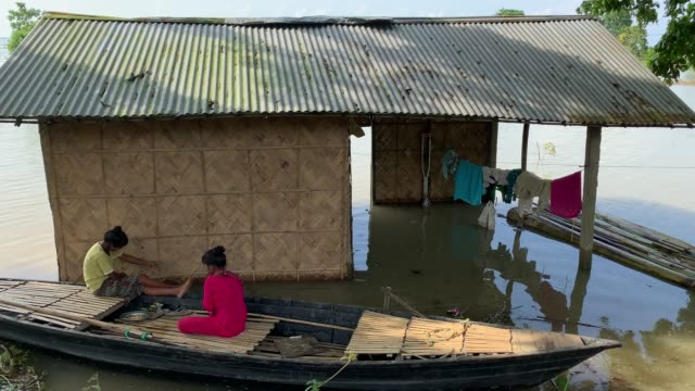 june 2020. girls take shelter on a boat after low lying areas were submerged due to heavy monsoon rain, at hatisila in kamrup district of assam in... - waten stock-videos und b-roll-filmmaterial