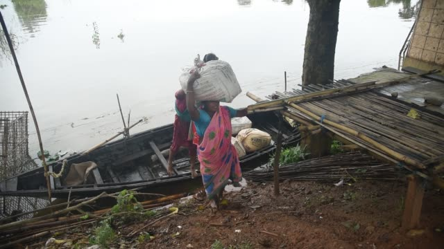 june 2020. people carry their belongings to a safer place on a boat over floodwater following heavy rainfall, at mayang village in morigaon district,... - waten stock-videos und b-roll-filmmaterial