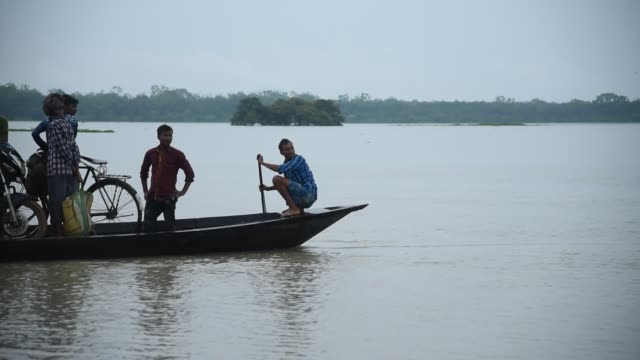 june 2020. people with their belongings move on a boat over floodwater following heavy rainfall, at mayang village in morigaon district, friday, june... - waten stock-videos und b-roll-filmmaterial