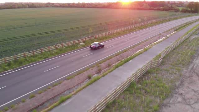 aerial view panning footage a car drives through a country road in cambridgeshire, uk - beauty in nature stock videos & royalty-free footage