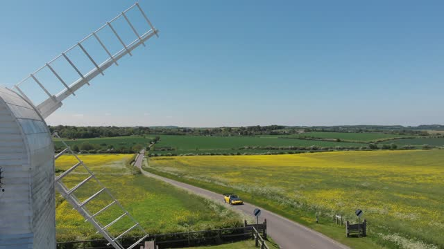 aerial view panning footage a car drives through a country road with a windmill in cambridgeshire, uk - beauty in nature stock videos & royalty-free footage