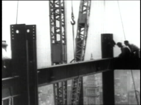 june 23 1930 ws workers guiding steel beam into place then fastening it down during empire state building construction / new york city new york... - empire state building video stock e b–roll