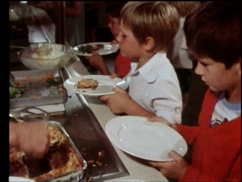 june 23, 1976 film montage school children having food put on plates by lunch ladies/ lunch ladies/ woman dishing up salad/ children in line/... - canteen stock videos & royalty-free footage