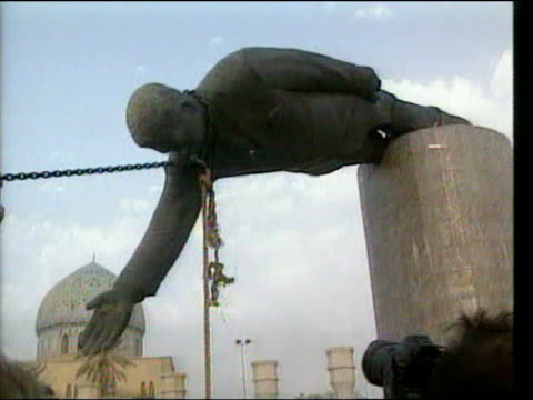 vídeos de stock e filmes b-roll de june 25 2005 ms spectators stand by taking photos as saddam hussein statue lies broken on pillar after being toppled/ baghdad iraq - estátua