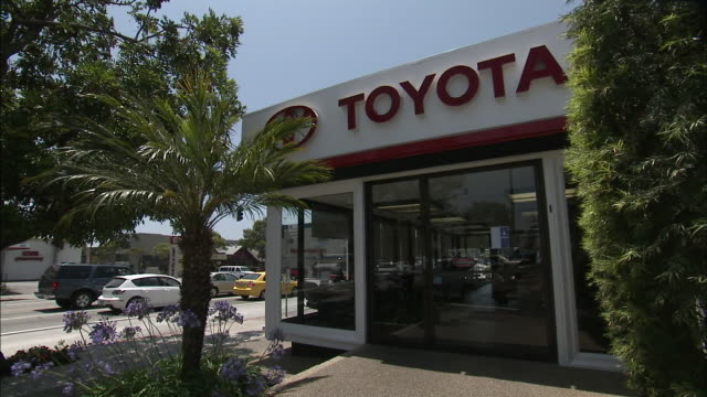 stockvideo's en b-roll-footage met june 30 2008 ws automobile dealership entrance with customer approaching and entering / detroit michigan united states - toyota motor