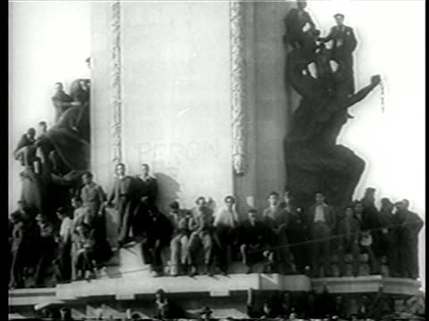 b/w june 4 1946 crowd sitting on statue celebrating inauguration of juan peron / buenos aires - 1946年点の映像素材/bロール
