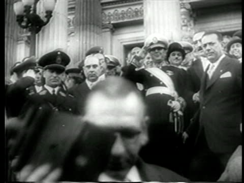 b/w june 4 1946 juan peron in uniform walking down steps saluting after inauguration / newsreel - 1946年点の映像素材/bロール