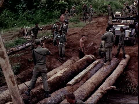 june 5, 1966 montage american combat engineers building a log bridge across a stream / dak to, vietnam - log stock videos & royalty-free footage