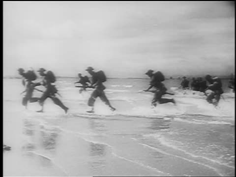 stockvideo's en b-roll-footage met june 6, 1944 soldiers carrying guns run in water to beach at normandy, france / d-day / doc. - geallieerde mogendheden